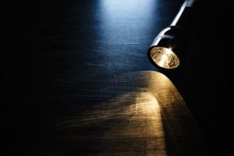A flashlight glows on a darkened surface