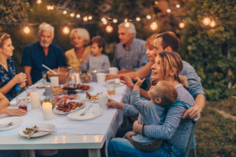 Photo of a big family during Thanksgiving dinner, celebrating holiday together in the backyard
