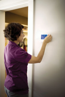 A woman sets the temperature on her digital thermostat