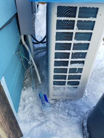 A ground mounted heat pump with snow removed from around the unit