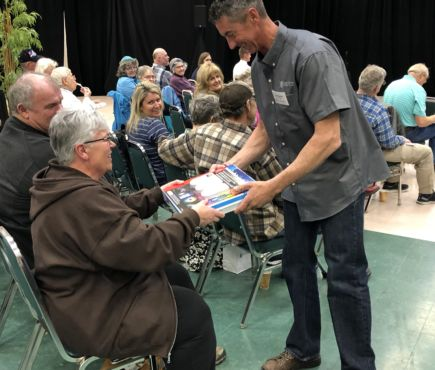 A CEC lineman hands out a door prize at the 78th Annual Meeting