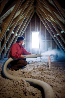 A licensed contractor blows insulation into an attic space.