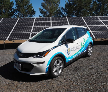 Central Electric Cooperative's new Chevy Bolt sits in front of solar panels at the solar community installation.