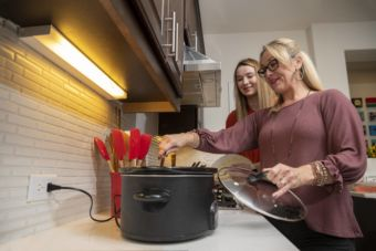 Mother and daughter use a slow cooker.