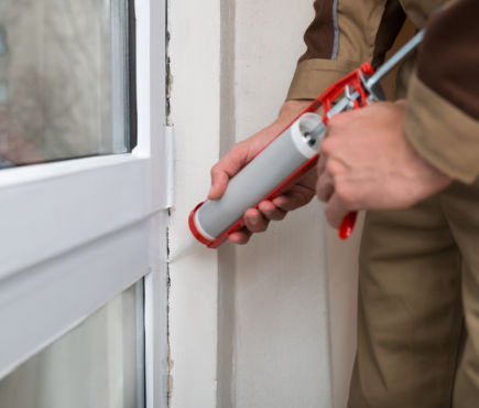 Close-up Of Person Hands Applying Silicone Sealant With Caulking Gun